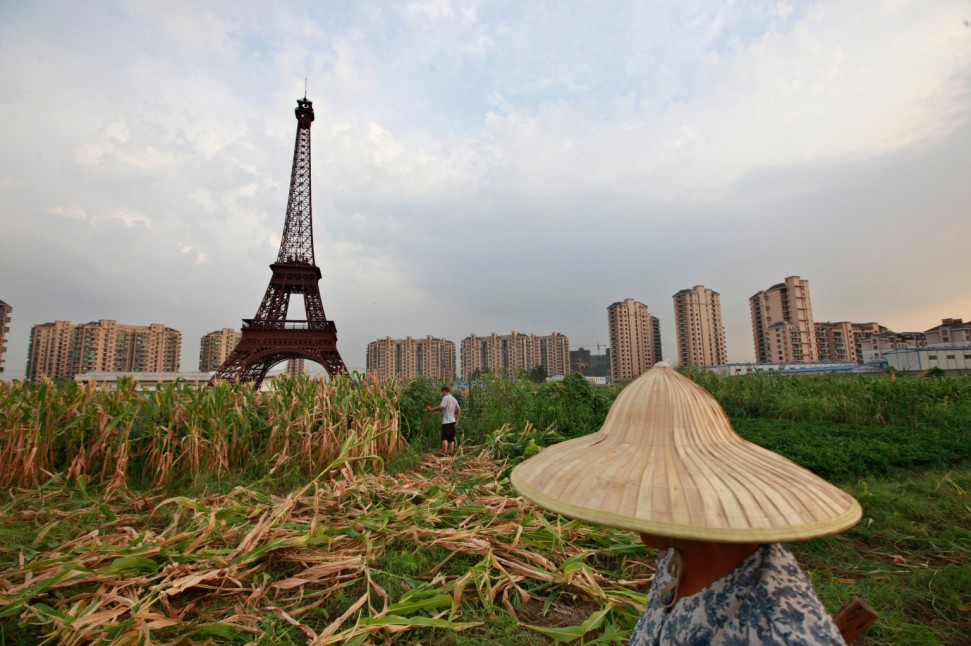 A farmer walks through a field near a replica of the Eiffel Tower at the Tianducheng development August 1, 2013. (REUTERS/Aly Song)