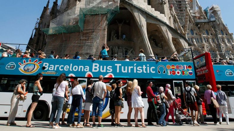 people-queue-up-at-a-city-tour-bus-stop-in-front-of-the-basilica-sagrada-familia-in-barcelona_5370533